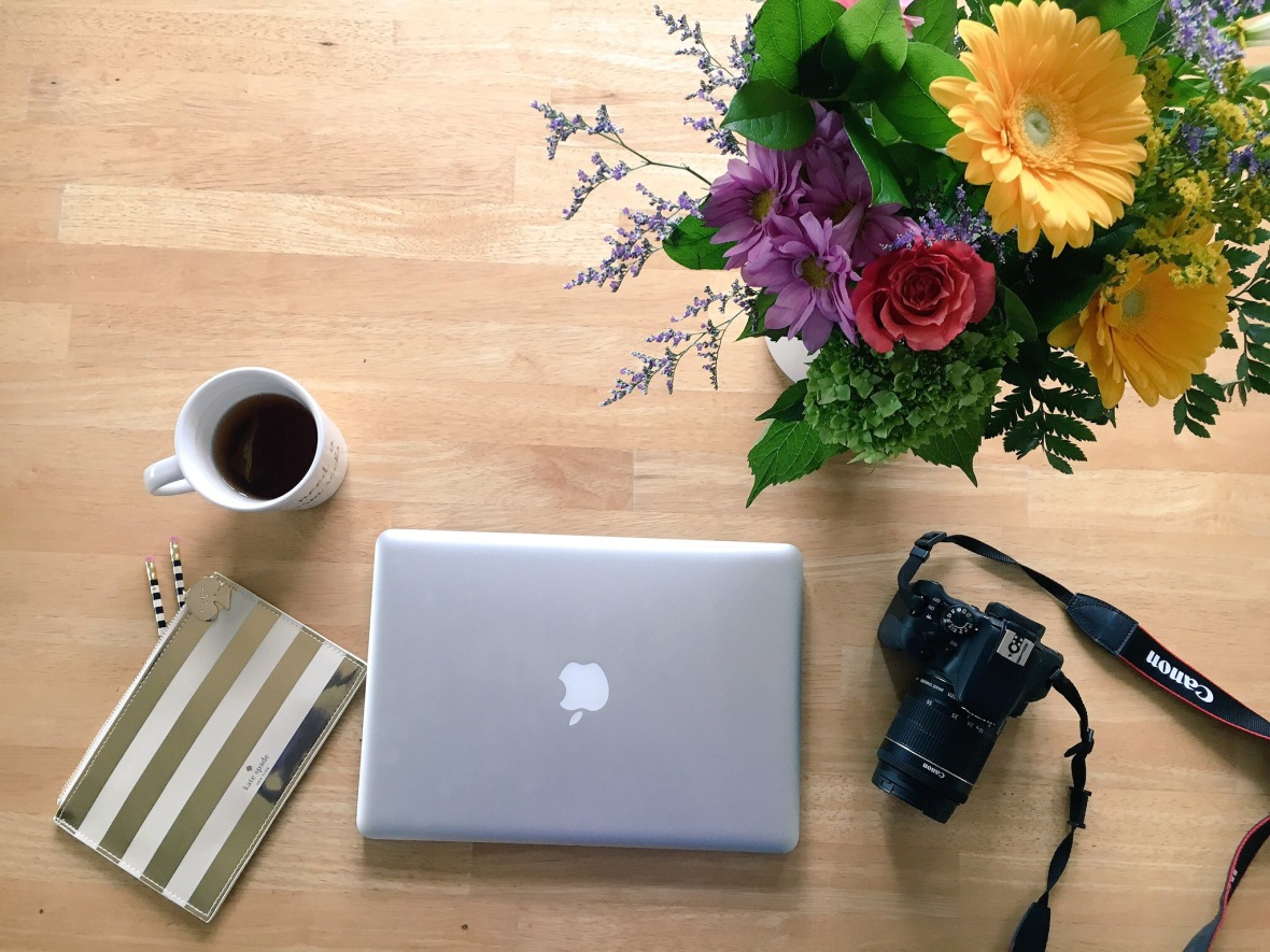 workspace - tea, pencil case, laptop, camera, flowers